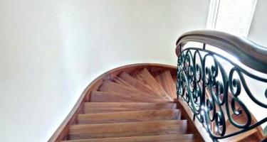 Деревянная лестница с кованным ограждением на тетивах