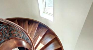 Винтовая лестница из дерева с кованными балясинами на тетивах