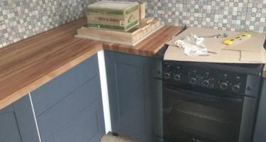 кухня с деревянной столешницей и фартуком